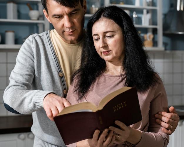 Vista frontal de um homem e uma mulher na cozinha lendo a bíblia