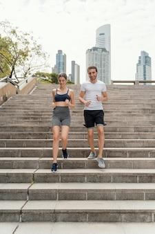 Vista frontal de um homem e uma mulher se exercitando nas escadas