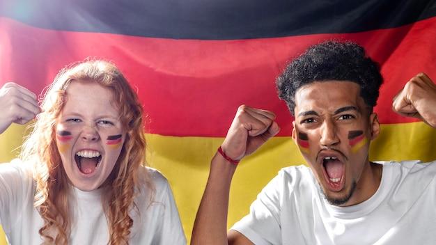 Vista frontal de um homem e uma mulher torcendo com a bandeira alemã