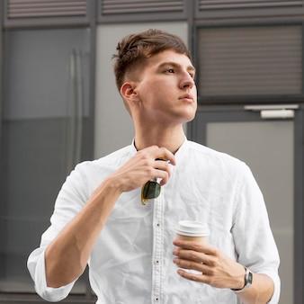 Vista frontal de um homem elegante posando enquanto toma um café ao ar livre