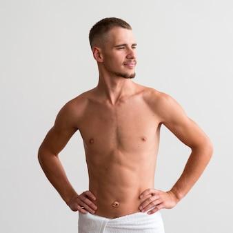 Vista frontal de um homem em uma toalha posando sem camisa