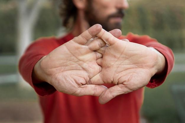 Vista frontal de um homem esticando os braços ao ar livre durante a ioga