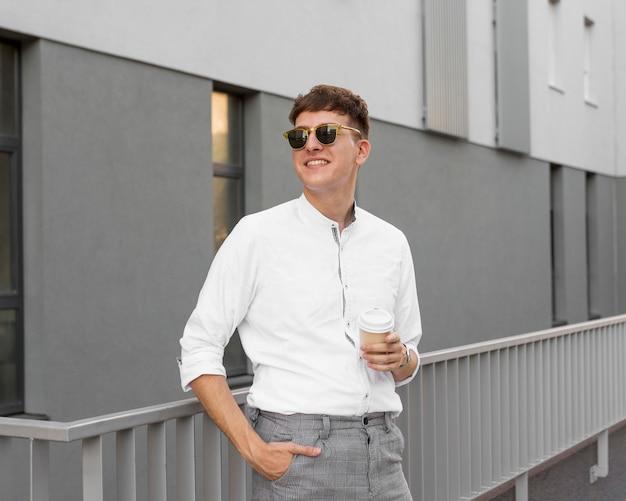 Vista frontal de um homem estiloso com óculos escuros segurando uma xícara de café ao ar livre