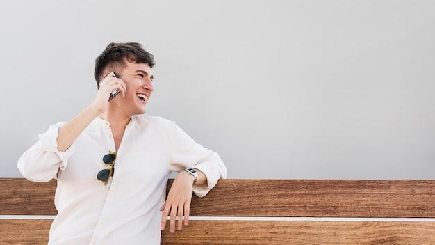 Vista frontal de um homem falando ao telefone ao ar livre com espaço de cópia