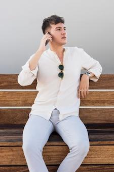 Vista frontal de um homem falando ao telefone ao ar livre