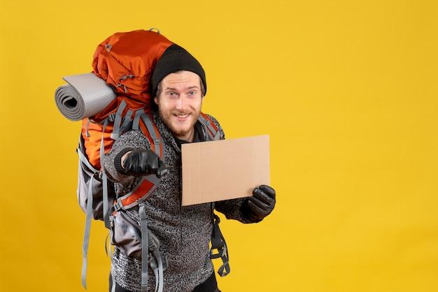 Vista frontal de um homem feliz caroneiro com luvas de couro e uma mochila segurando um papelão em branco, dando um soco no punho