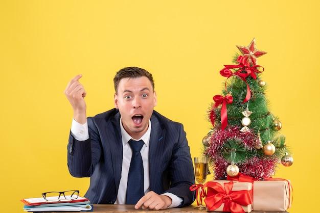 Vista frontal de um homem feliz fazendo sinal de dinheiro sentado à mesa perto da árvore de natal e presentes em amarelo