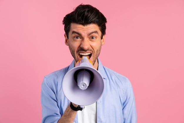 Vista frontal de um homem gritando em um megafone