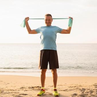 Vista frontal de um homem idoso sorridente malhando com uma corda elástica na praia
