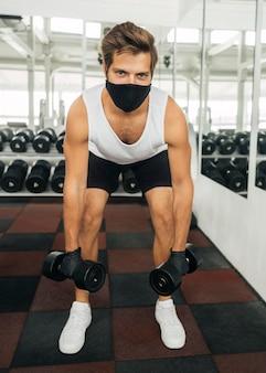 Vista frontal de um homem malhando na academia com máscara médica