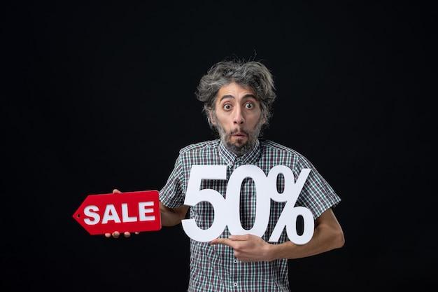 Vista frontal de um homem muito confuso segurando uma marca e uma placa vermelha de venda na parede escura