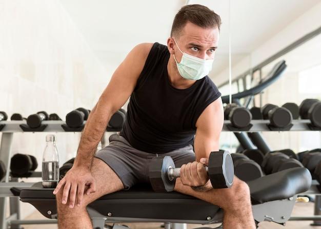 Vista frontal de um homem na academia com máscara médica malhando