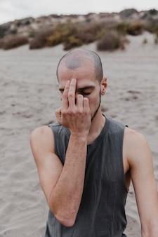 Vista frontal de um homem na praia exercitando a consciência plena de ioga