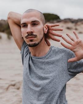 Vista frontal de um homem na praia fazendo ioga