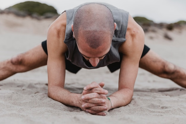 Vista frontal de um homem na praia fazendo posições de ioga na areia