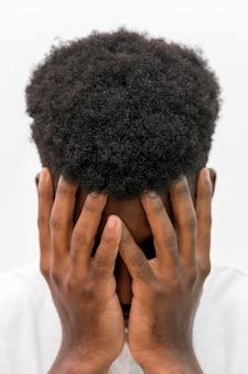 Vista frontal de um homem negro chorando com as mãos cobrindo o rosto