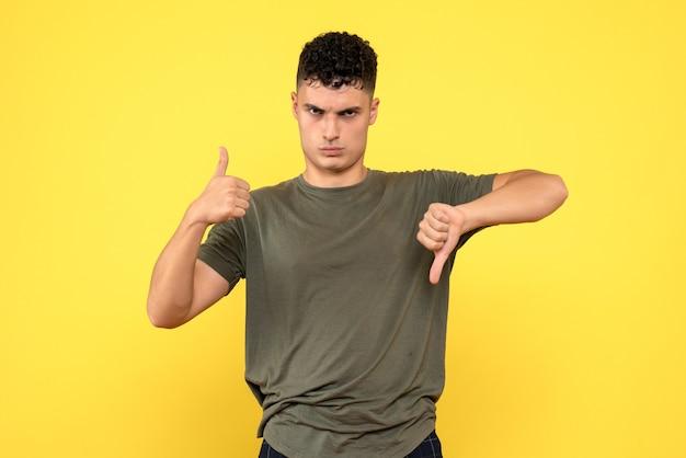 Vista frontal de um homem, o homem descontente mantém os polegares para cima e para baixo