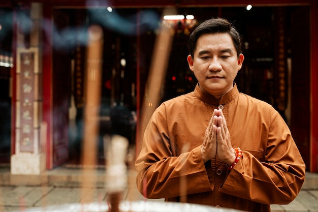 Vista frontal de um homem orando no templo com incenso