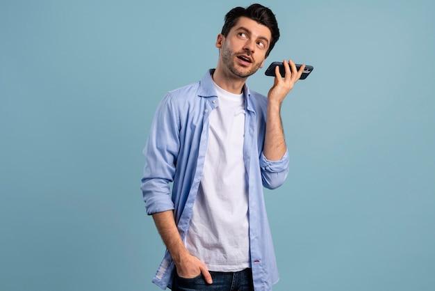 Vista frontal de um homem ouvindo seu smartphone