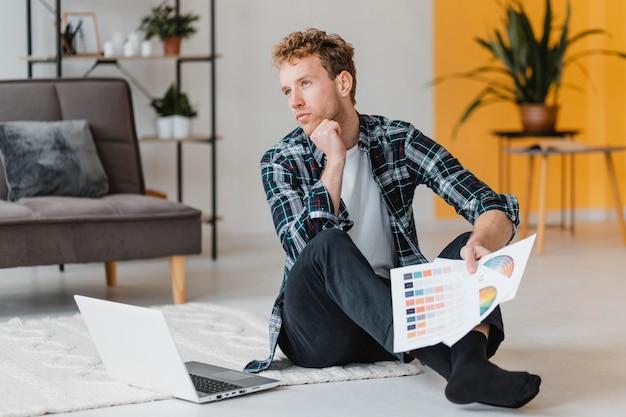 Vista frontal de um homem planejando redecorar a casa