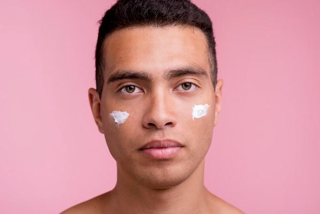 Vista frontal de um homem posando com creme facial