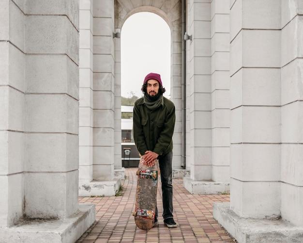 Vista frontal de um homem posando com seu skate na cidade