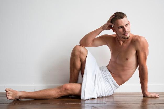 Vista frontal de um homem posando sem camisa em uma toalha