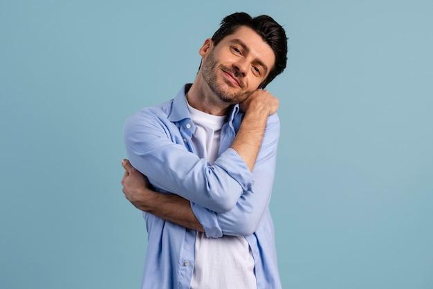 Vista frontal de um homem se abraçando, mostrando amor-próprio