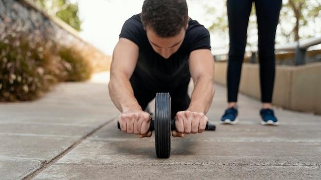 Vista frontal de um homem se exercitando com uma roda abdominal do lado de fora