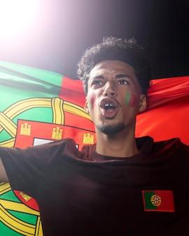 Vista frontal de um homem segurando a bandeira de portugal