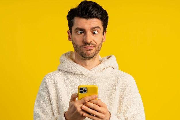 Vista frontal de um homem segurando um smartphone e fazendo careta