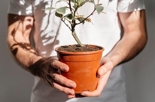 Vista frontal de um homem segurando um vaso de planta