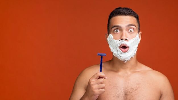 Vista frontal de um homem sem camisa com espuma de barbear no rosto segurando uma navalha