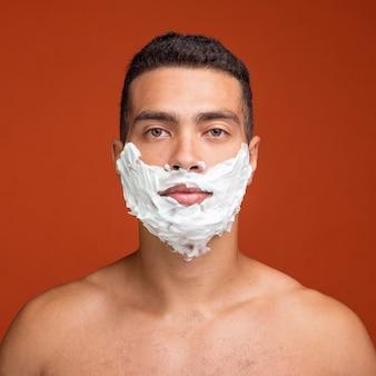 Vista frontal de um homem sem camisa com espuma de barbear no rosto