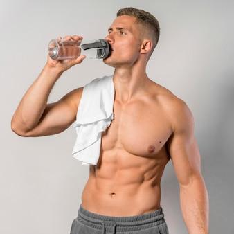 Vista frontal de um homem sem camisa com uma toalha e água potável