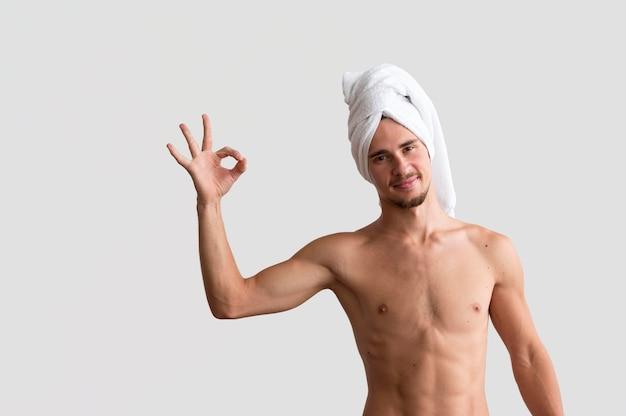 Vista frontal de um homem sem camisa com uma toalha na cabeça, fazendo o sinal de ok