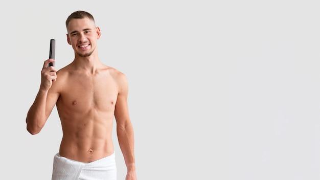 Vista frontal de um homem sem camisa em uma toalha segurando o pente