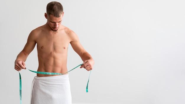 Vista frontal de um homem sem camisa em uma toalha segurando uma fita métrica com espaço de cópia