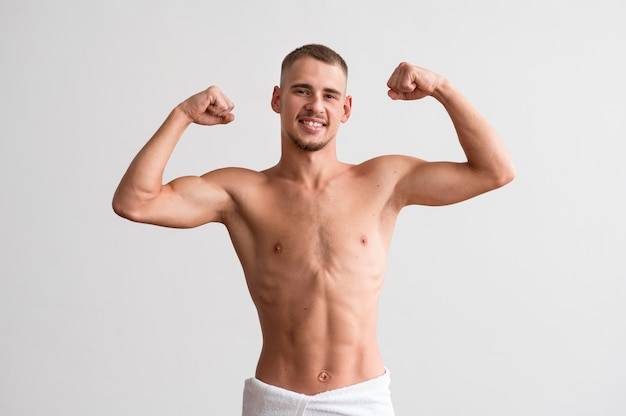 Vista frontal de um homem sem camisa exibindo seus bíceps