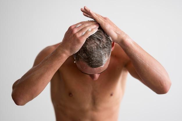 Vista frontal de um homem sem camisa lavando o cabelo com shampoo