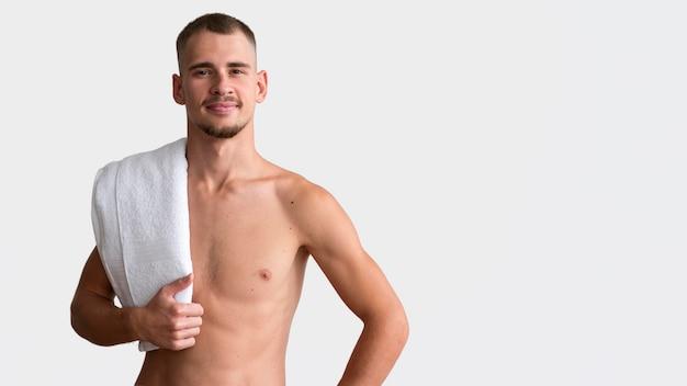 Vista frontal de um homem sem camisa posando com uma toalha e copie o espaço