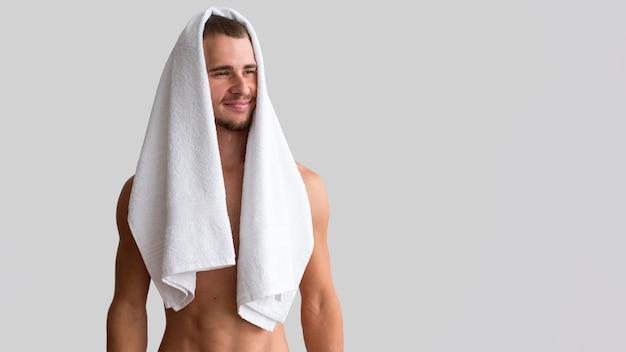 Vista frontal de um homem sem camisa posando com uma toalha sobre a cabeça