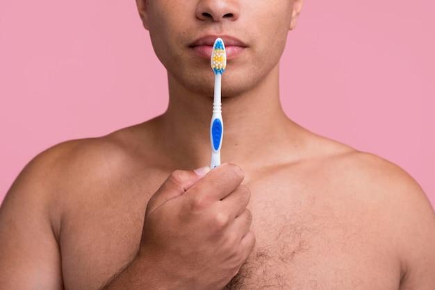 Vista frontal de um homem sem camisa segurando a escova de dentes perto da boca