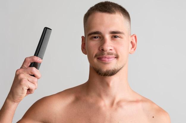 Vista frontal de um homem sem camisa segurando um pente