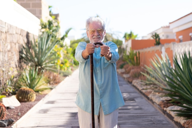 Vista frontal de um homem sênior sorridente atraente ao ar livre, olhando para a câmera segurando uma bengala