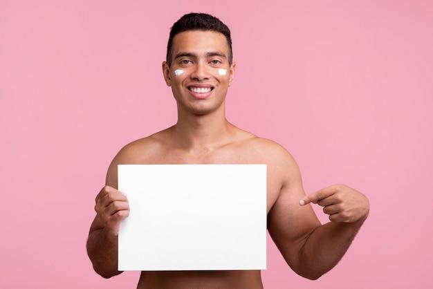 Vista frontal de um homem sorridente com creme no rosto apontando para um cartaz em branco
