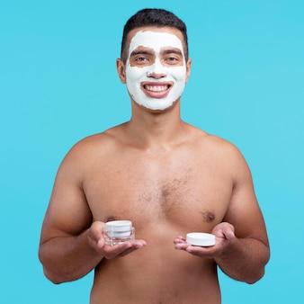 Vista frontal de um homem sorridente com máscara facial de beleza e segurando creme