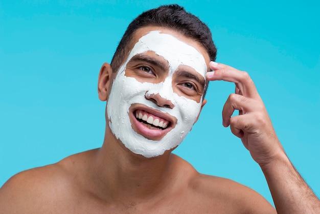Vista frontal de um homem sorridente com máscara facial de beleza