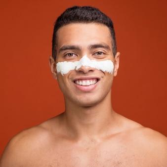 Vista frontal de um homem sorridente com máscara facial