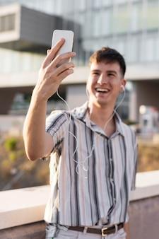 Vista frontal de um homem sorridente fazendo uma videochamada ao ar livre